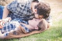 engaged couple in a field wearing flannels kissing