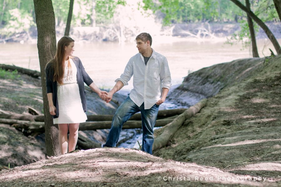a couple walks by the river together for portraits with a Belle Plaine Wedding Photographer