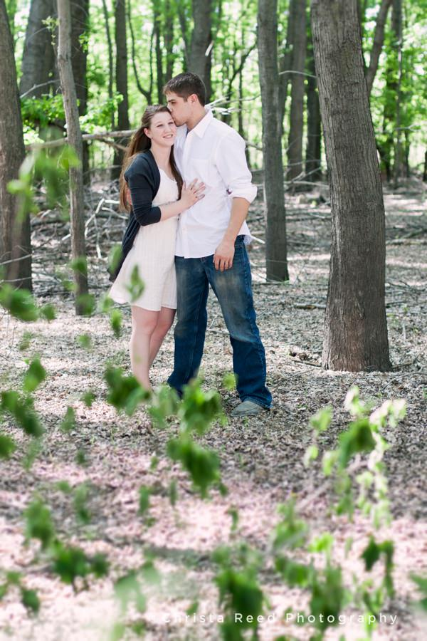 a couple poses for spring anniversary portraits in the woods by a couple holds their wedding rings for an anniversary portrait by Belle Plaine Wedding Photographer