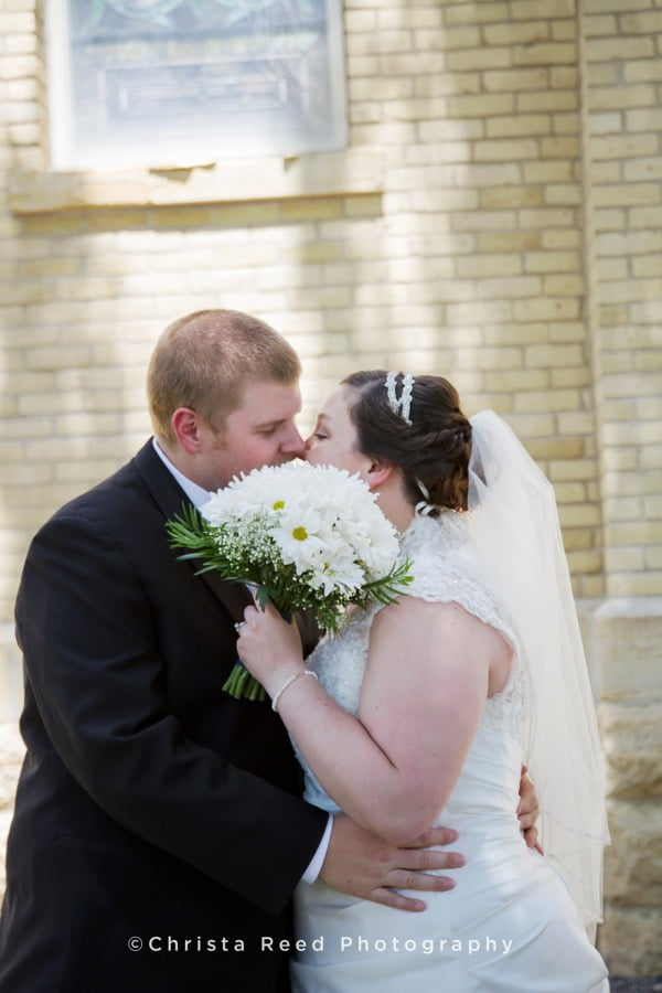 bride and groom kiss behind bride's daisy bouquet