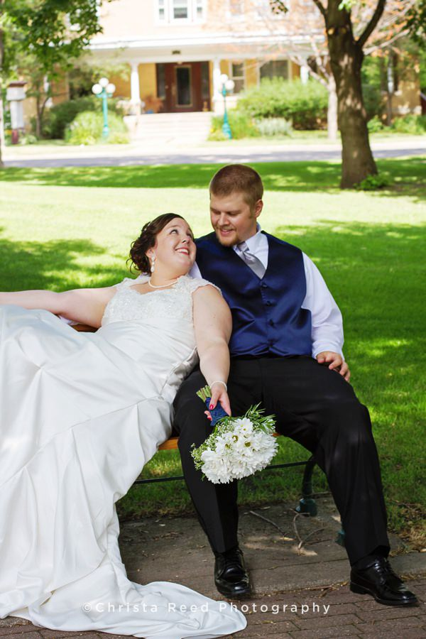 bride and groom sit on bench in chaska for wedding portraits