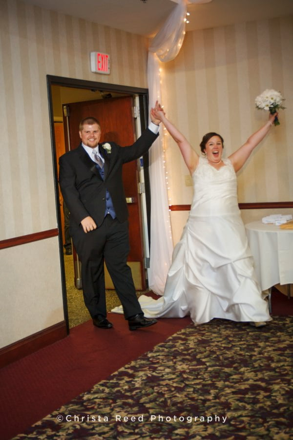 bride and groom make an exciting entrance to their wedding reception