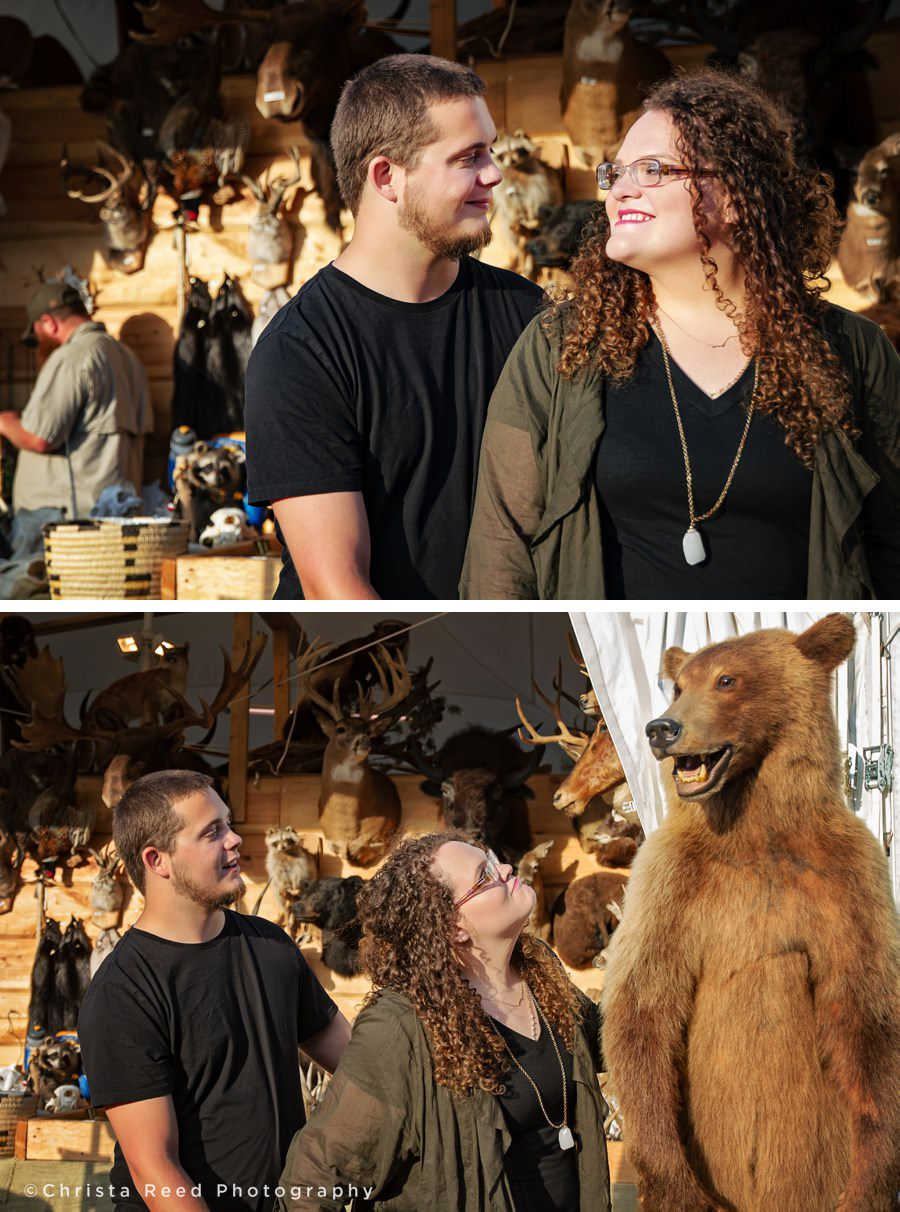 couple poses in front of a taxidermy shop for their Minnesota state fair engagement shoot