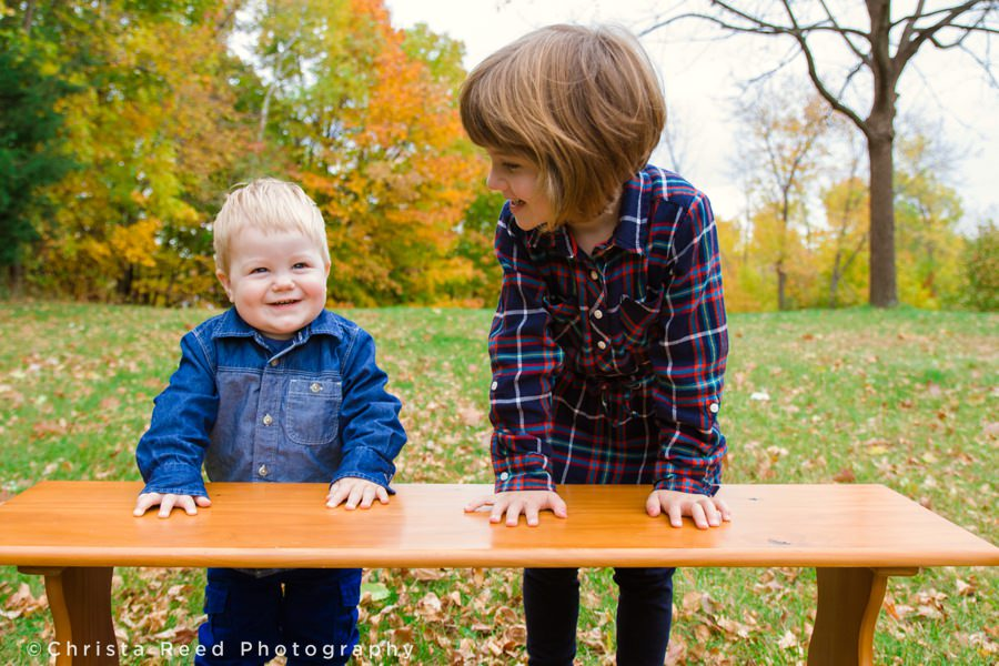 brother and sister laughing in field with leaves for fall portraits