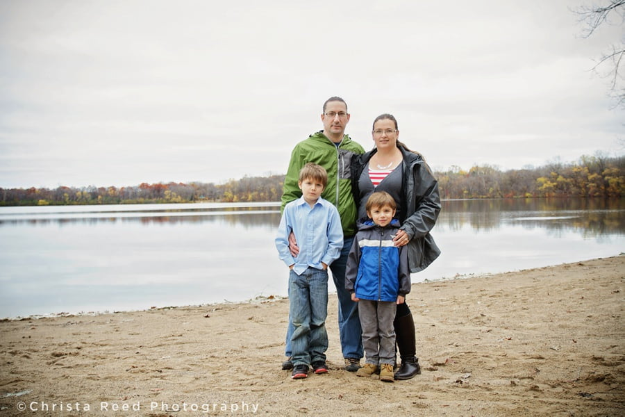 a family of four standing together at lake ann beach