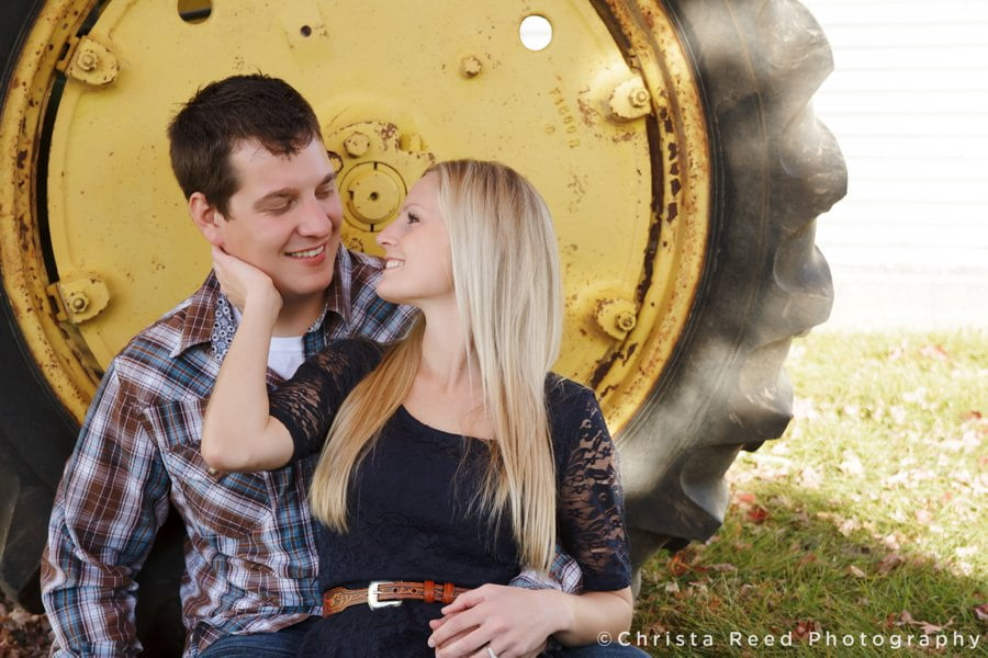 engaged couple sits together next to tractor for fall engagement portraits in belle plaine