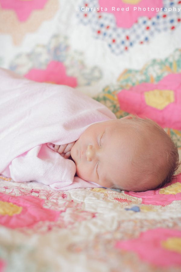 newborn sleeping wrapped in pink blanket for photo shoot