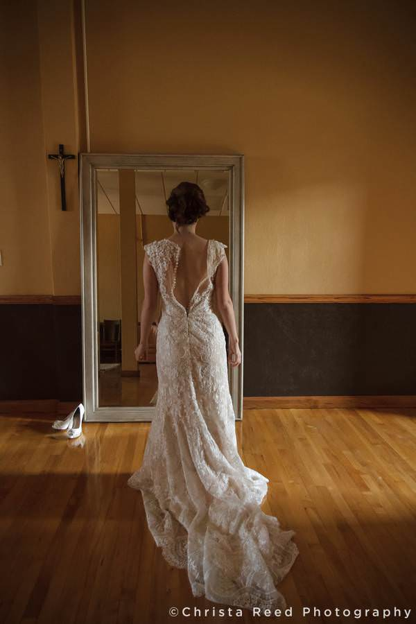 dramatic picture of a mankato bride standing in front of a mirror in her wedding dress at St. Peter and Paul Catholic Church