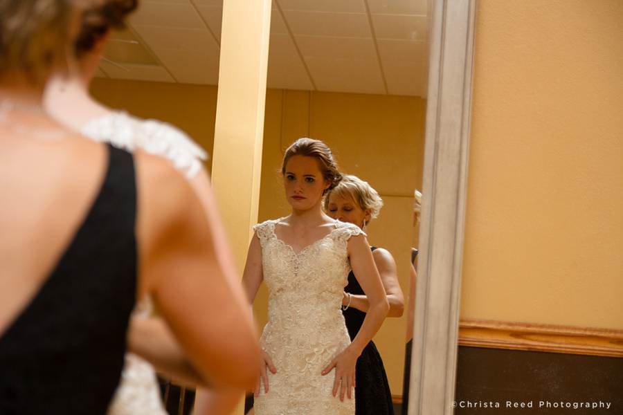 bride looks in the mirror while mother buttons her dress in before her wedding in mankato