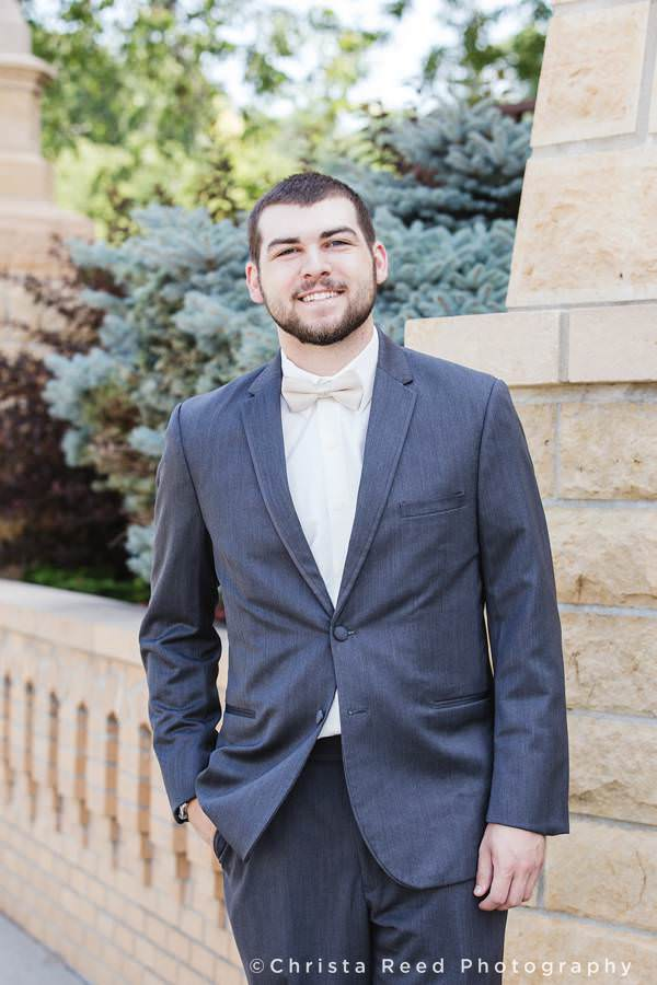 groom poses for a portrait outside St. Peter and Paul Church before his wedding in Mankato