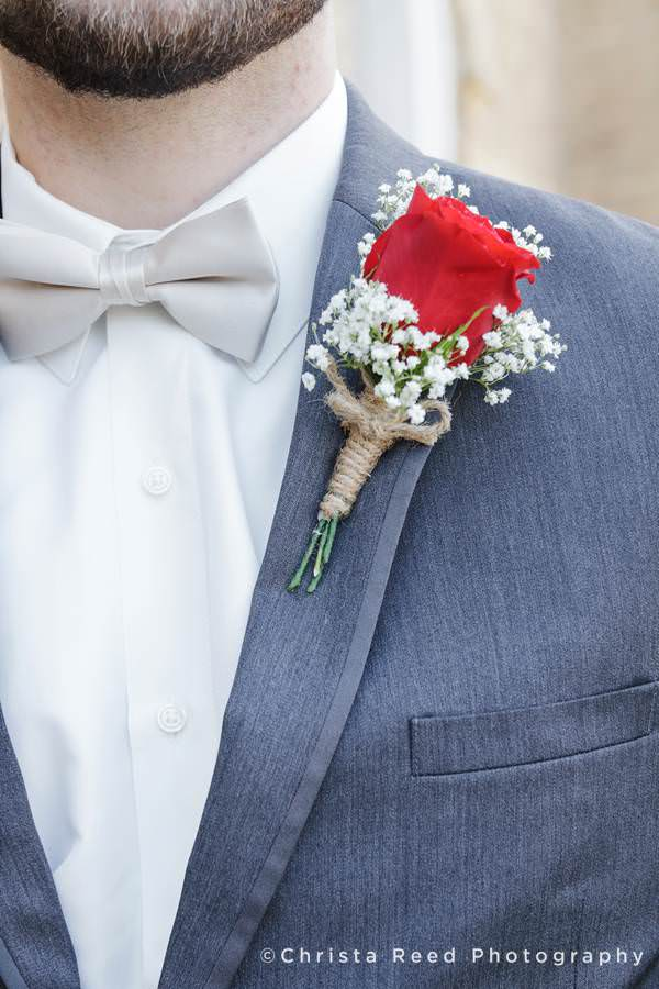 close of of rose boutonnière with baby's breath on grey suit for a Mankato wedding mass