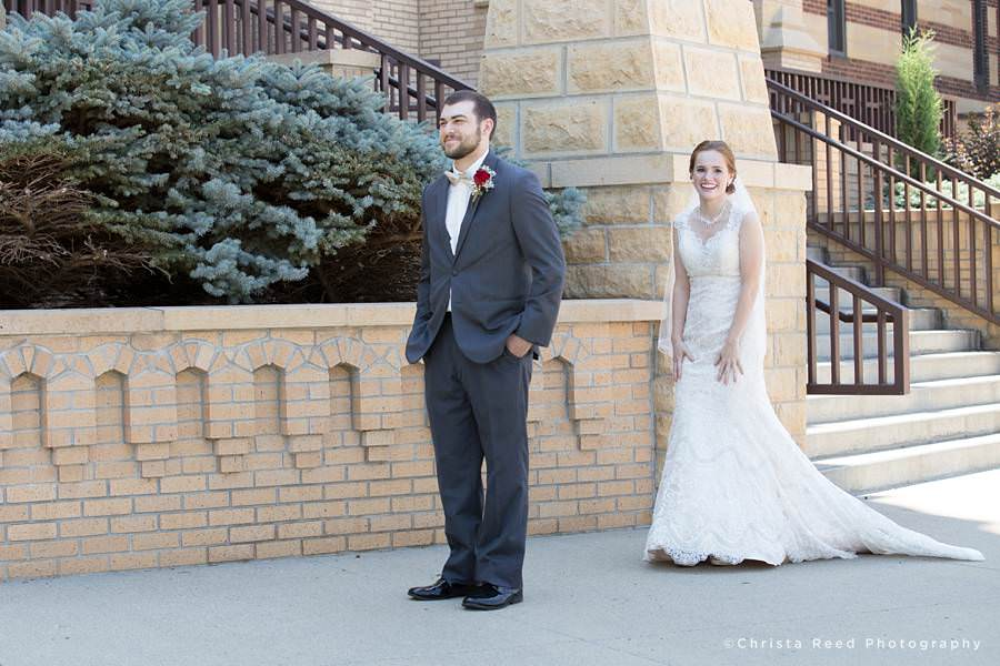 bride and groom have a first look outside St. Peter and Paul Catholic church in mankato before their wedding