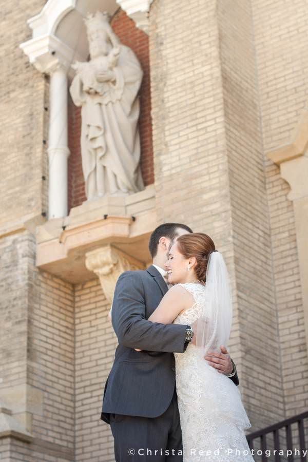 bride and groom hold each other outside the church before their wedding mass in mankato