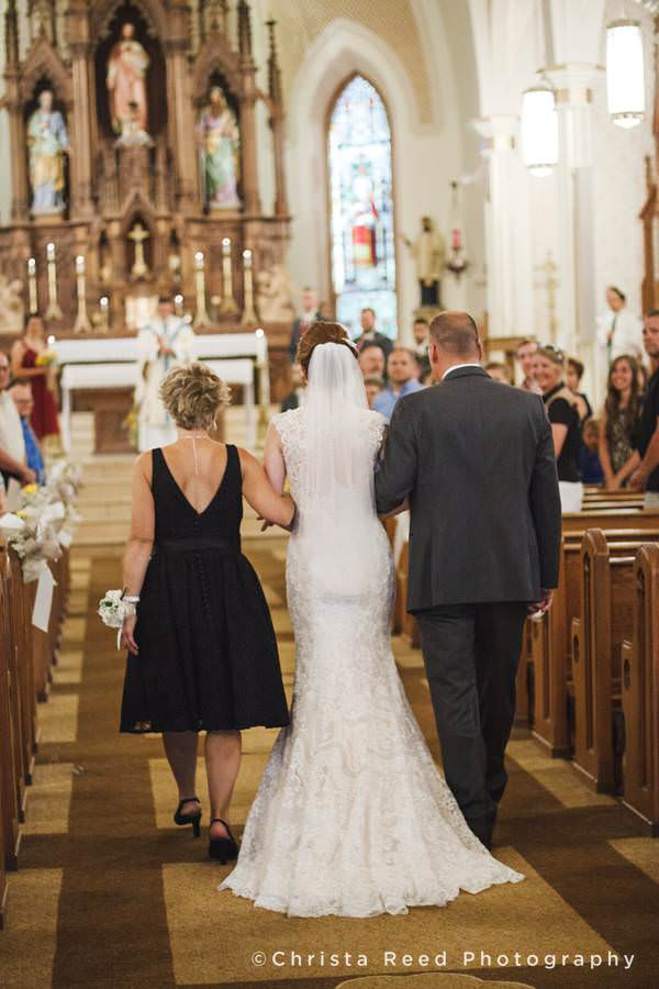 bride walks down the aisle arm and arm with parents at st peter and Paul church in mankato