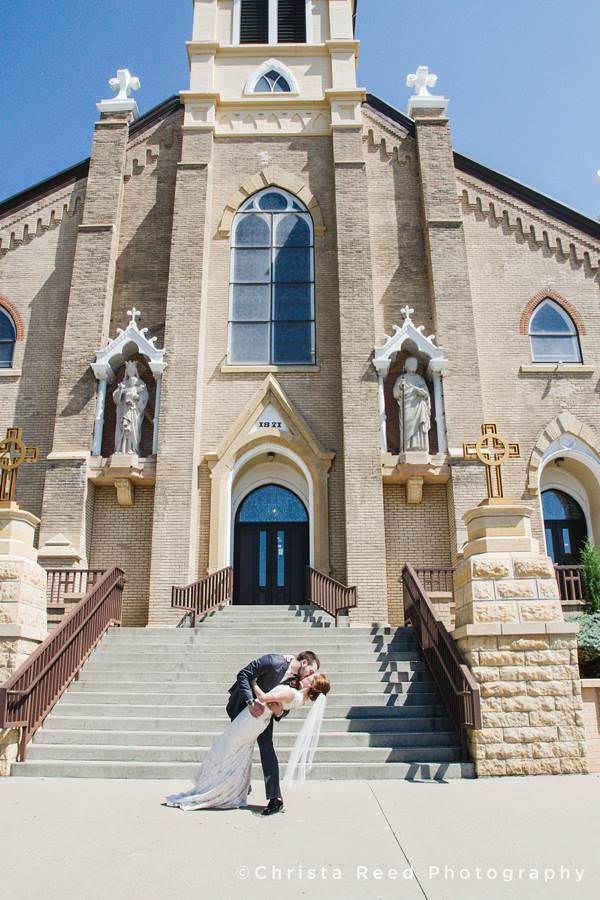 wedding couple kissing in front of the church in mankato