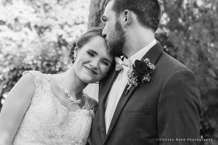 groom kisses bride on forehead after mankato wedding