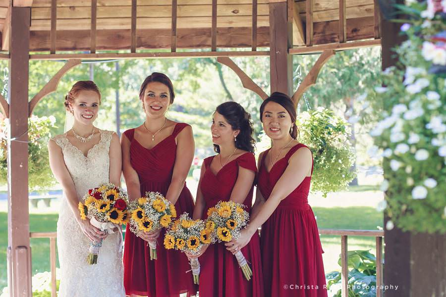 bridesmaids in mankato wear red dresses and hold sunflowers for fourth of july wedding