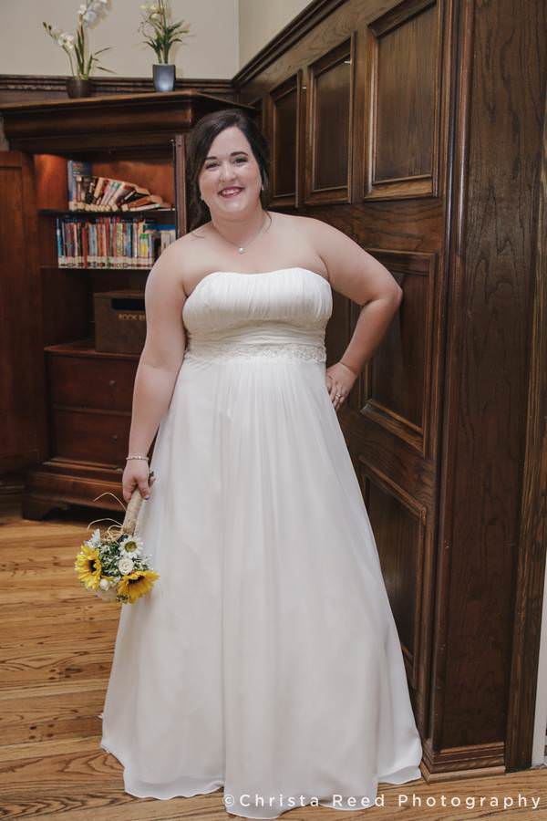bride poses next to book case