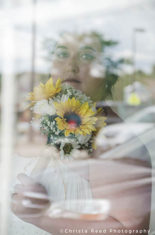 bride with her bouquet and reflections in window