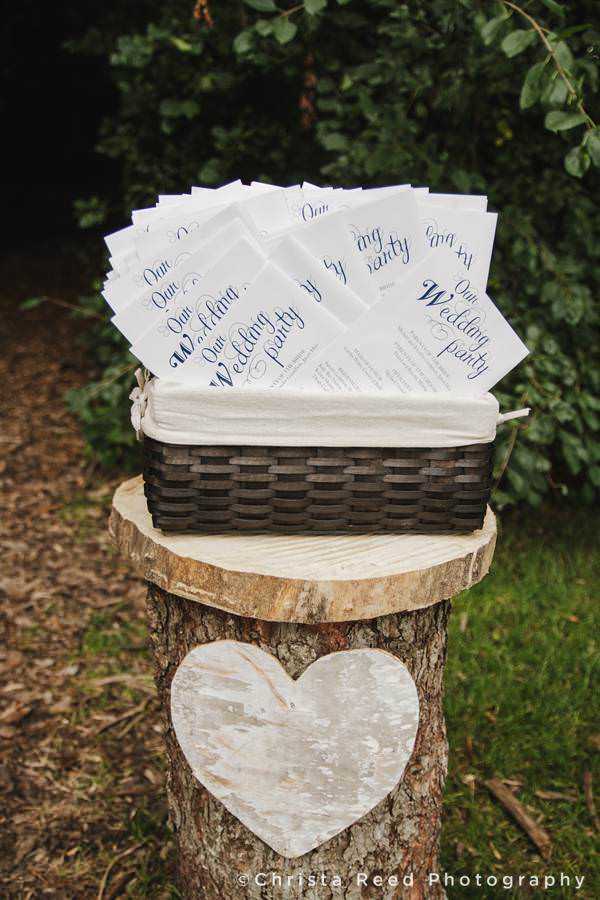 wedding programs in a basket on top of a log