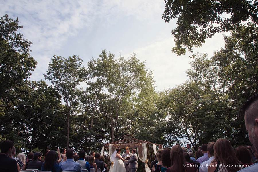 sun shines through trees at outdoor wedding ceremony