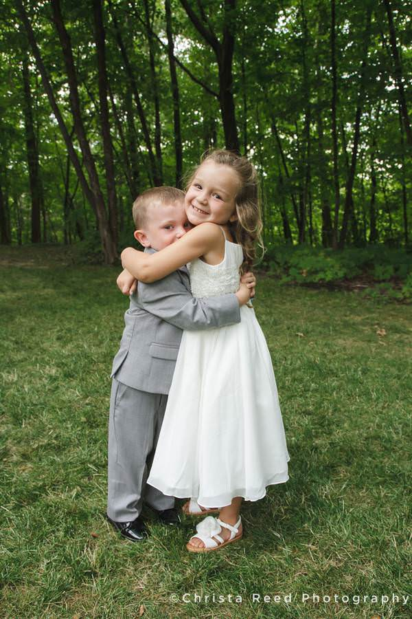 adorable flower girl hugs ring bearer