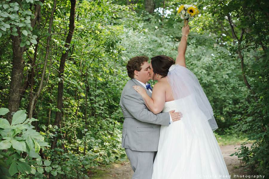 bride holds bouquet up and kisses groom