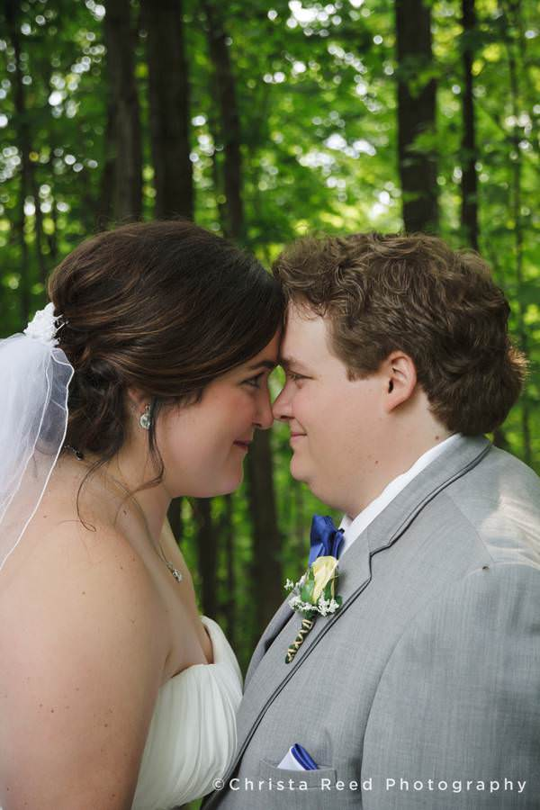 bride and groom touch foreheads in the woods