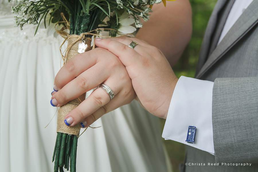 bride and groom hold hands to show their rings