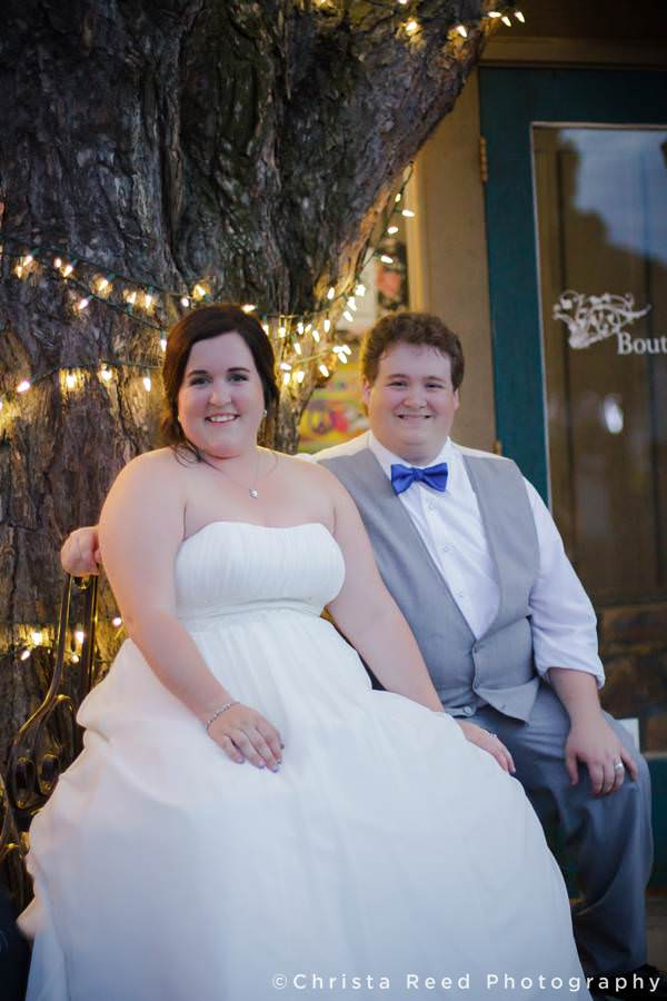 couple sitting next to tree with white lights in chanhassen