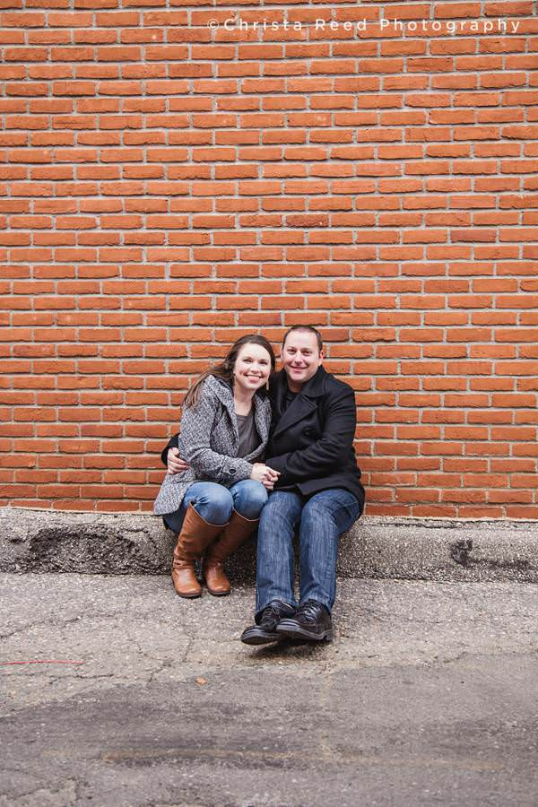 a couple sits in front of a brick wall for their engagement portraits in shakopee