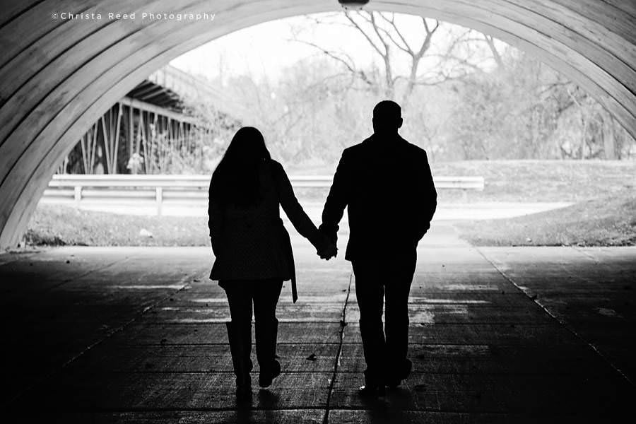 a couple holds hands and walks through the tunnel in shakopee Minnesota for their engagement photos