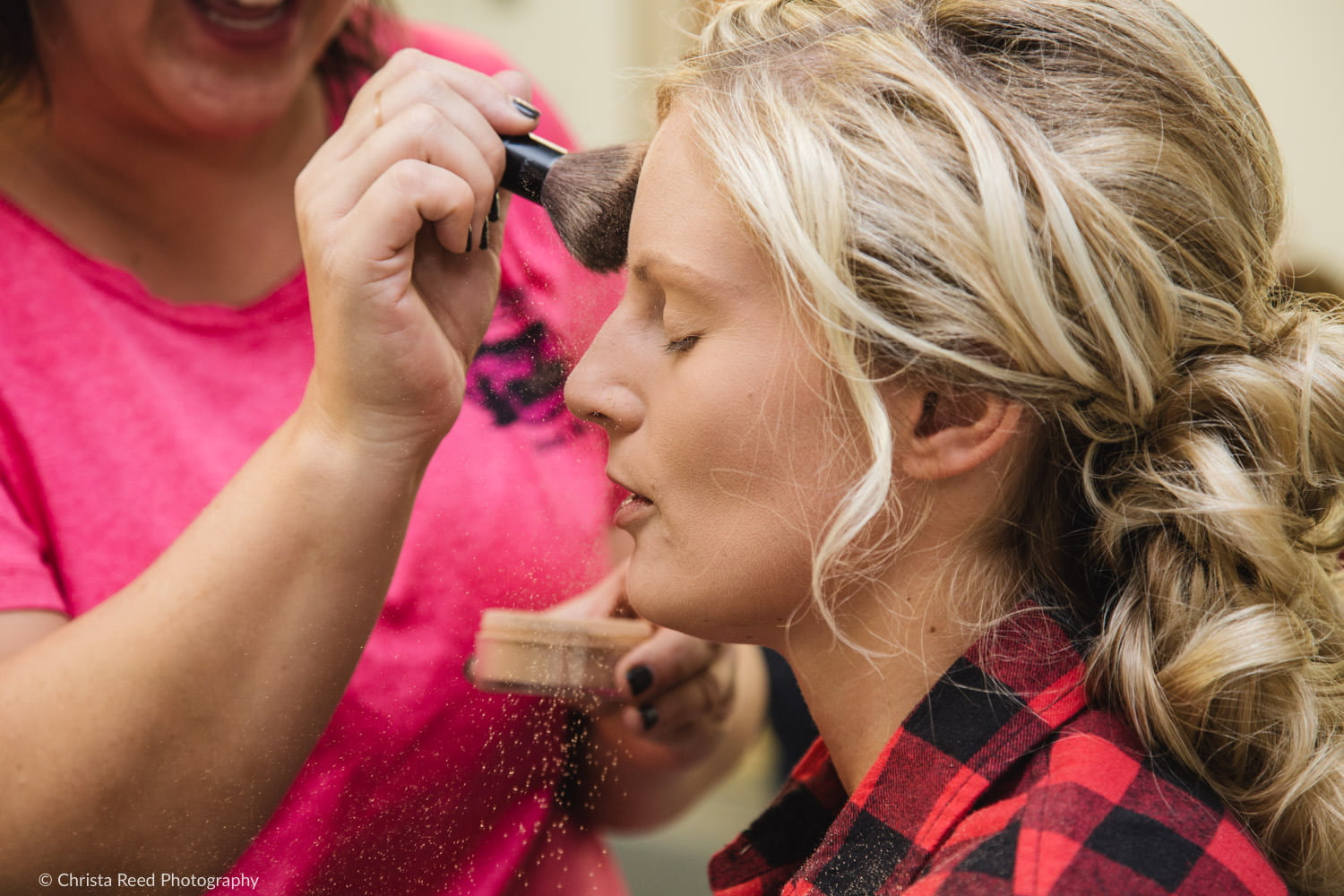 a bride gets her make up done in a flannel shirt for her farm wedding in minnesota