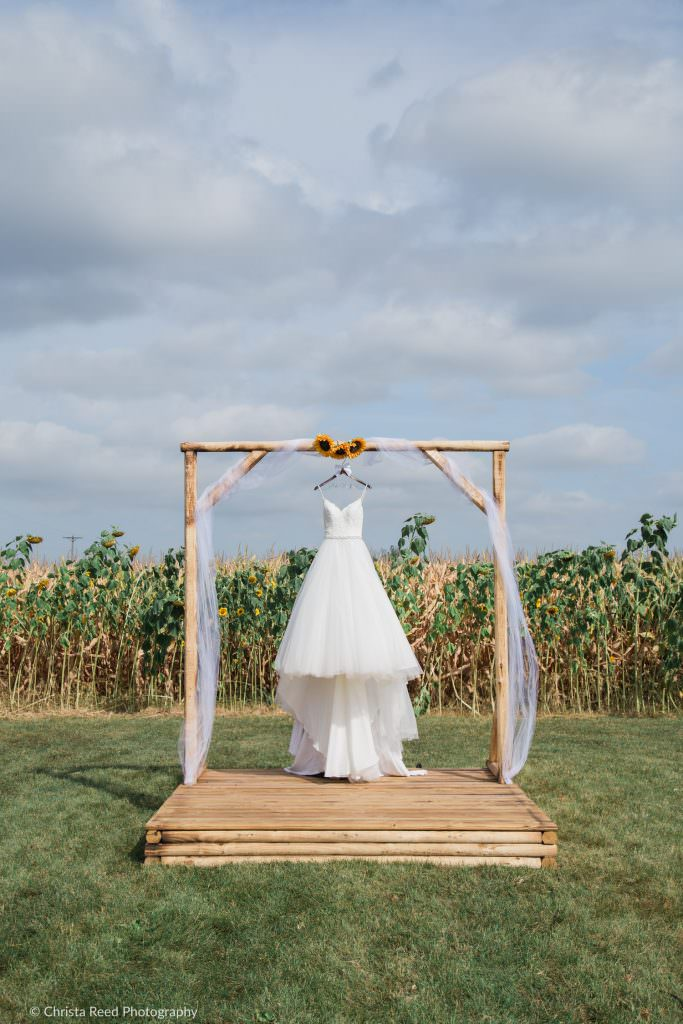 wedding dress in a cornfield with flowers before a belle plaine Minnesota wedding