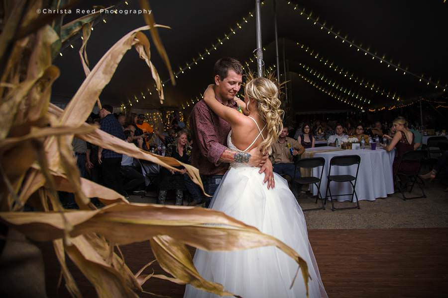 a couple has their first dance at a Belle Plaine farm wedding reception decorated with corn