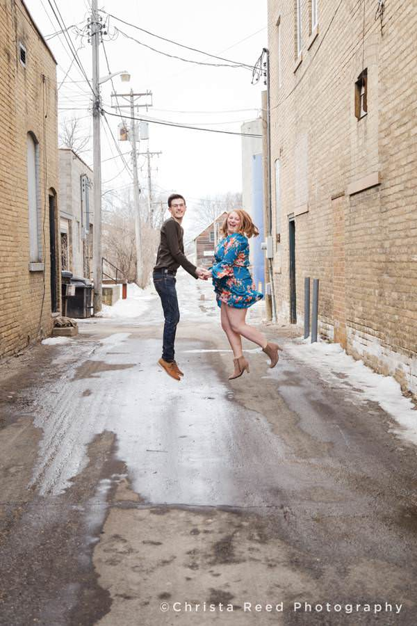 fun pictures of a couple jumping for joy by Minnesota Couples Photographer