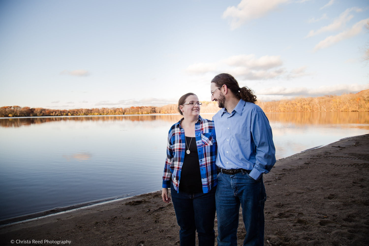 a couple poses for fall portraits next to lake Ann in Chanhassen