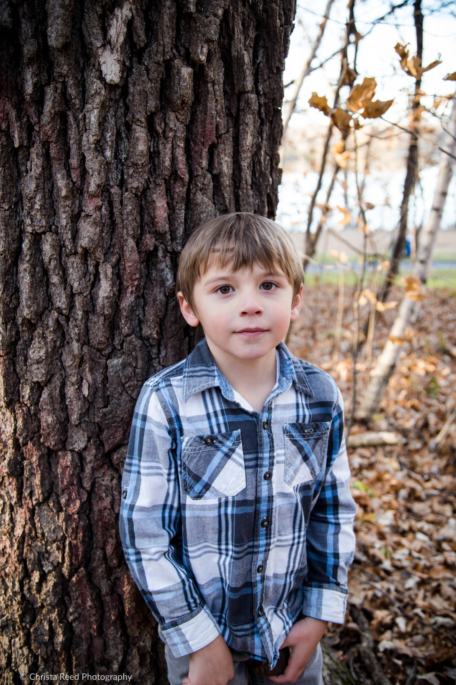 a boy in a flannel shirt poses for his photo shoot at Lake Ann